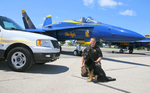 Hero Napór - photo of the dog with officer from K9 police department in the United States in the background of Blue Angel plane